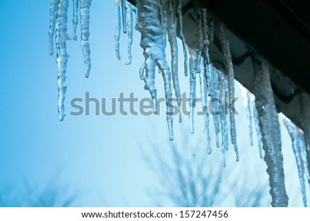 beautiful icicles glint in the sun against the blue sky Royalty-Free Stock Photo #157247456