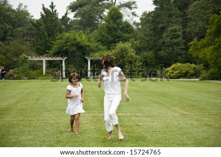 Woman and child running in grass at park #15724765