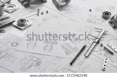 Engineer technician designing drawings mechanicalparts engineering Engine manufacturing factory Industry Industrial work project blueprints measuring bearings caliper tools Royalty-Free Stock Photo #1572482248