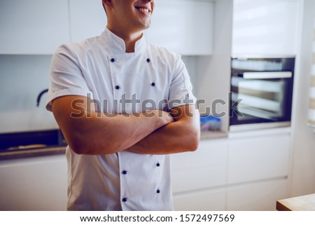 Cropped picture of handsome smiling caucasian male chef in uniform standing in kitchen with arms crossed.