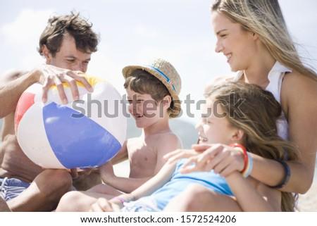 Father holding beach ball with beach ball on beach #1572524206