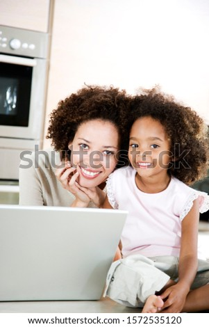 Mother and daughter with laptop in the kitchen at home #1572535120