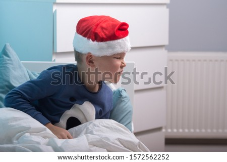 Funny child boy in Santa Clause hat and pajamas waking up in Christmas morning. Happy child sleep in white bed in child bedroom at home. Happy Xmas and New Year holiday! Christmas gift.  #1572562252