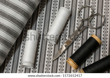 Scissors with spools of white and black thread. #1572652417