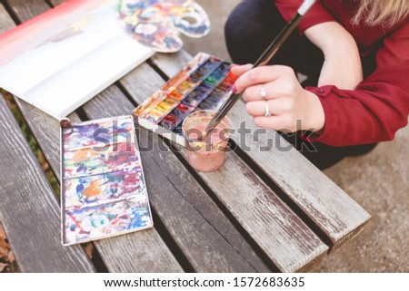 Woman draws a picture on a park bench. Blonde artist engaged in her favorite hobby of drawing.  Drawing accessories #1572683635