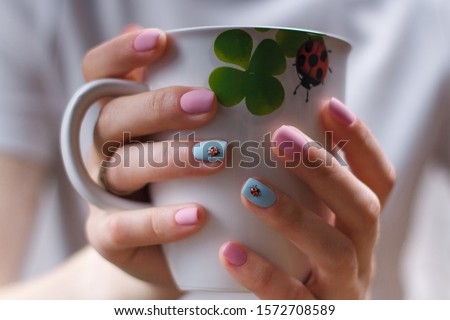 Girlish manicure with volumetric ladybugs on pink and blue fingernails. Female hands holding a cup with lady-bird and clover leaf picture. Spring nail art design. Hands care and beauty concept.
