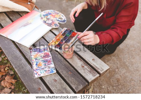 Woman draws a picture on a park bench. Blonde artist engaged in her favorite hobby of drawing.  Drawing accessories #1572718234