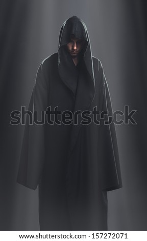 a guy in a black robe standing in the dark under the rays of the moon #157272071