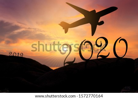 silhouette of a plane on colorful sky in the evening with text two zero one nine and two zero two zero. #1572770164