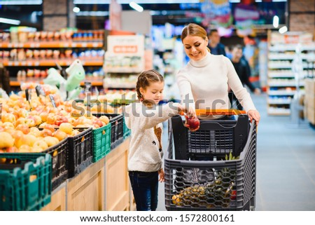 Family in the supermarket. Beautiful young mom and her little daughter smiling and buying food. The concept of healthy eating. Harvest #1572800161