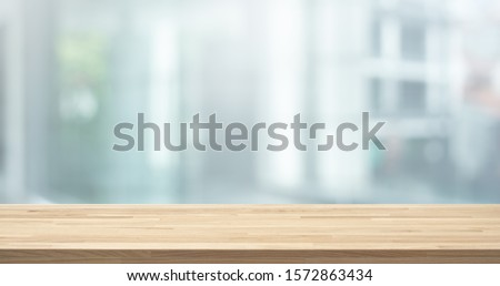 Selective focus of wood table top on white wall glass (big window) background.For montage product display or design key visual layout #1572863434