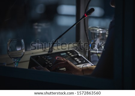 Translator or translation booth at a conference. Hand of a person for simultaneous translating is seen working in a booth. Glass of water next to a translator. Royalty-Free Stock Photo #1572863560