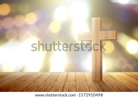 Christian cross on the wooden floor with blurred lights background