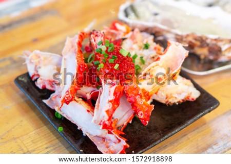 Alaskan king crab legs on with salmon fish roe topping garnish with spring onion garnish #1572918898