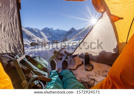 Foot of the Belukha Mountain in winter, a tent on the side of the mountain. man sits and looks out of the tent #1572924571