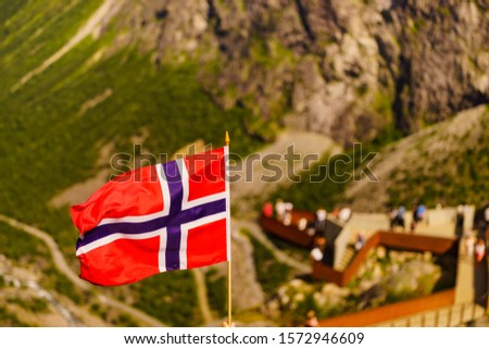Trollstigen mountain road landscape in Norway, Europe. Norwegian flag waving and many tourists people on viewing platform in background. National tourist route. #1572946609