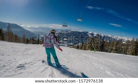 Snowboarding girl going down the slope in Bad Kleinkirchheim, Austria. The slopes are perfectly groomed.There is a ski lift above the girl. Lots of snow caped mountains. Winter sports activity in Alps #1572976138