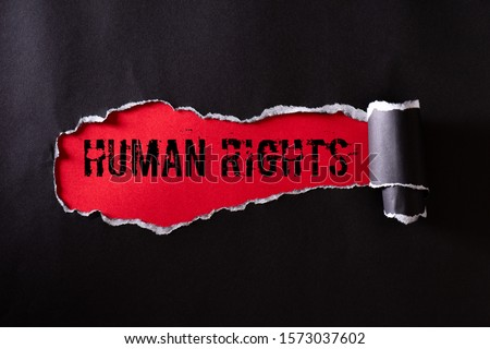 Top view of Black torn paper and the text HUMAN RIGHTS on a red background. Human rights concept. #1573037602