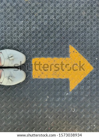 woman stand  beside yellow arrow on steel iron bridge floor to walk in same direction. vintage girl green shoes with grey iron background. abstract pavement start point guidance route way road street #1573038934