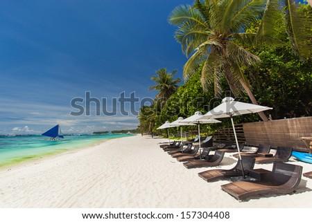 Sun umbrellas and beach chairs on tropical coastline, Philippines, Boracay  #157304408