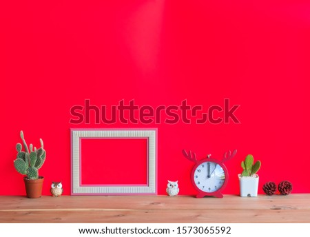 Beautiful  cactus,blank  wooden  picture  frame,simulated  owls,watch  clock  and  pine  cone  on  wood  table  with  red  background