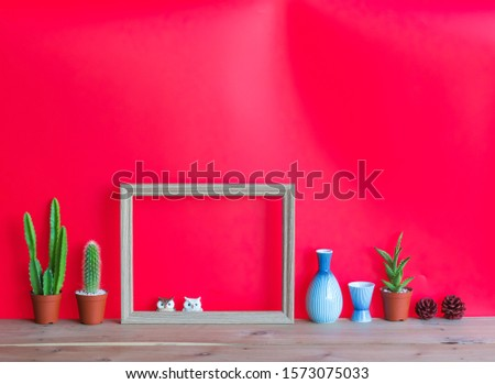 Beautiful  cactus,blank  wooden  picture  frame,simulated  owl ,ceramic  bottle  and  pine  cone  on  wood  table  with  red  background