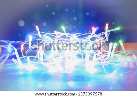 Christmas garland is brightly lit on a blurred background. Bright, colorful and festive lights. #1573097578