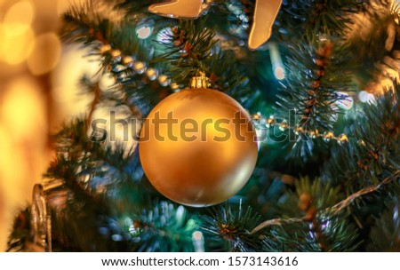 Christmas tree with gold bauble ornaments. Decorated Christmas tree closeup. Balls and illuminated garland with flashlights. New Year baubles macro photo with bokeh. Winter holiday light decoration #1573143616