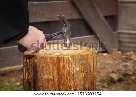 A man hammers a nail into a wooden log with a hammer #1573203154