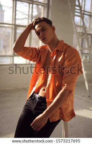 handsome guy model with cool haircut portrait portrait with sunbeams on his face and cool eyes  and a shadow on his face