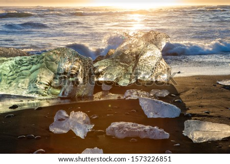 Icebergs on the cost of the black sand beach in the rays of the rising sun,  Jokulsarlon,  south Iceland. #1573226851