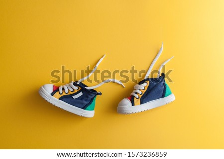 Colorful baby shoes on bright yellow background in child's room Royalty-Free Stock Photo #1573236859