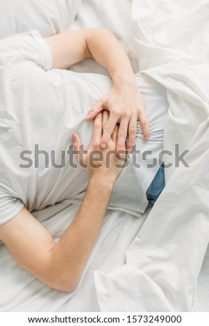 cropped view of man lying on white bedding and suffering from abdominal pain #1573249000