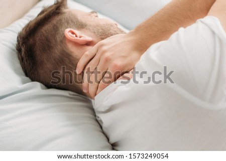 young man lying in bed and suffering from neck pain #1573249054