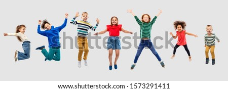 childhood, motion and happiness concept - happy little children jumping in air over grey background #1573291411