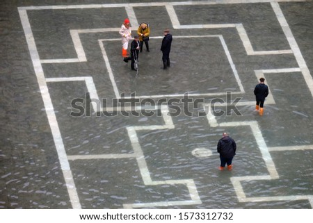 """People walk on the flooded St. Mark's square in background, after an exceptional overnight """"Alta Acqua"""" high tide water level in Venice, Italy November 27, 2019  #1573312732"""