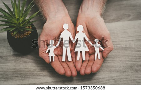 Hands protecting a family; symbol of life insurance Royalty-Free Stock Photo #1573350688
