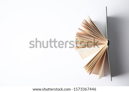 Open book on white background, top view Royalty-Free Stock Photo #1573367446