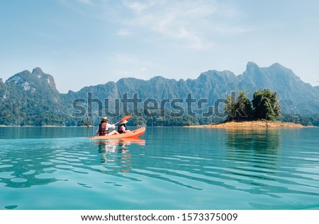 Mother and son floating on kayak together on lake in Thailand	 #1573375009
