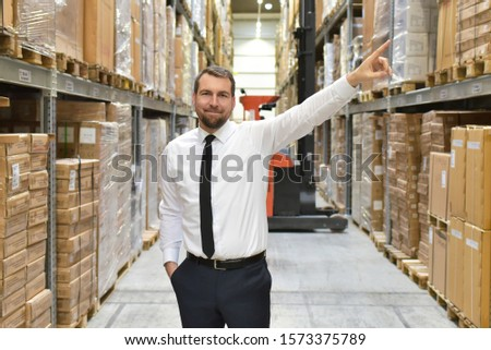 portrait friendly businessman/ manager in suit working in the warehouse of a company #1573375789