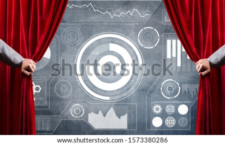 Hand opening red curtain and drawing business graphs and diagrams behind it #1573380286