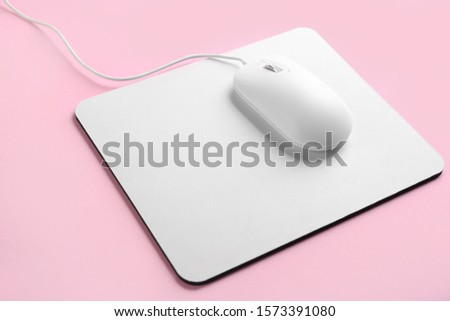 Modern wired optical mouse and pad on pink background Royalty-Free Stock Photo #1573391080