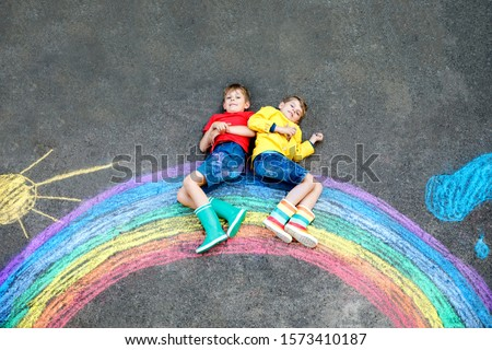 two school kids boys having fun with with rainbow picture drawing with colorful chalks on asphalt. Siblings, twins and best friends in rubber boots painting on ground playing together.