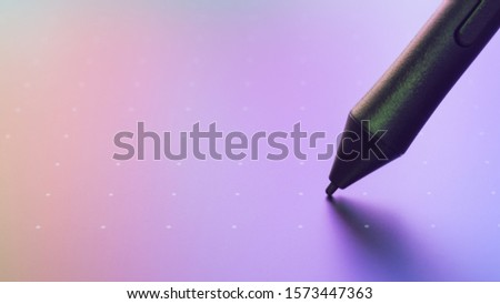Close up shot of Graphic tablet with pen for illustrators and designers. Colorful color reflect on tablet from screen monitor. Graphic design instrument background concept. #1573447363