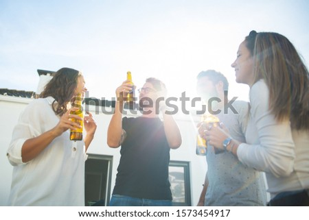 Happy carefree friends drinking beer, dancing and having fun on outdoor terrace. Young men and women in casual meeting outside. Party outside concept #1573454917