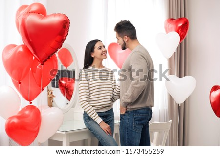 Lovely young couple in room decorated with heart shaped balloons. Valentine's day celebration #1573455259