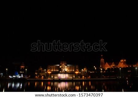 Szczecin. Night view from across the river to the illuminated historic center. Odra river. Chrobry embankments in Szczecin Royalty-Free Stock Photo #1573470397