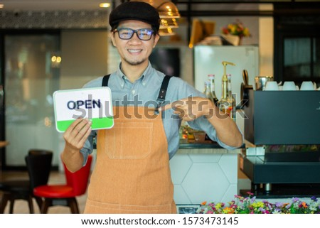 small business owner standing with coffee machine in his own coffee shop holding cup of coffee.man holding an opening sign while opening #1573473145