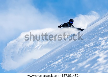 Powerful image of a snowboarder in fresh powder with clear sky #1573514524
