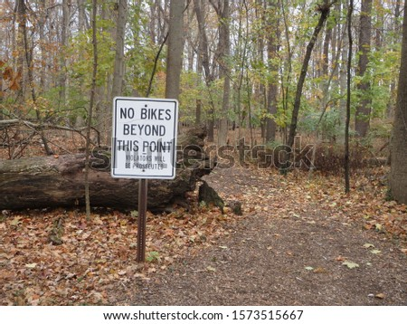 Entrance to a trail through a forest with fallen trees and a No Biking sign, on an autumn day in Columbus, Ohio
